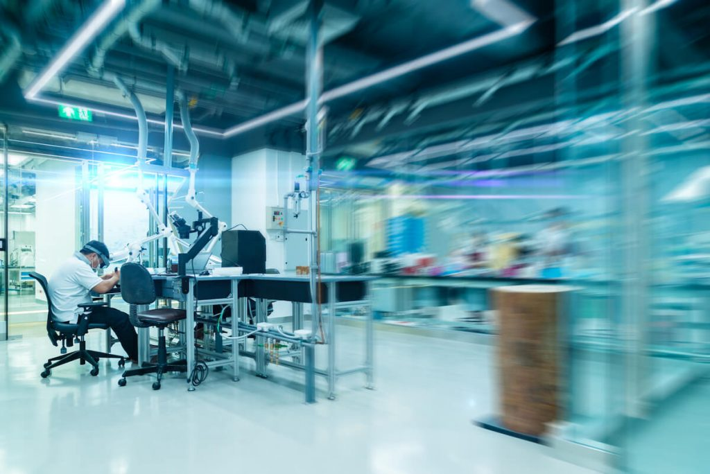 Scientist is working in a modern laboratory and production indoor with abstract blur. 1